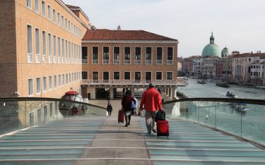 """VENICE, ITALY - MARCH 9: Tourists are seen with their luggage as they cross the Calatrava bridge towards the railway station as they try to leave a completely empty city on March 9, 2020 in Venice, Italy. Prime Minister Giuseppe Conte announced a """"national emergency"""" due to the coronavirus outbreak and imposed quarantines on the Lombardy and Veneto regions, which contain roughly a quarter of the country's population. Italy has the highest number of cases and fatalities in Europe.  The movements in and out are allowed only for work reasons, health reasons proven by a medical certificate.The justifications for the movements needs to be certified with a self-declaration by filling in forms provided by the police forces in charge of the checks. (Photo by Marco Di Lauro/Getty Images)"""