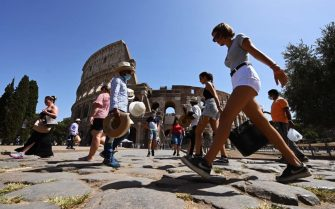 Tourists, some wearing a face mask, walk by the Colosseum monument on August 22, 2020 in Rome during  the COVID-19 infection, caused by the novel coronavirus. - Italy has recorded its highest number of coronavirus infections since May 23, with 845 new cases reported over the last day, health ministry officials said on August 20. Italy in May emerged from a severe lockdown after becoming one the first European countries to report cases of COVID-19. (Photo by Vincenzo PINTO / AFP) (Photo by VINCENZO PINTO/AFP via Getty Images)