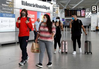 Travellers, some wearing a face mask or covering due to the COVID-19 pandemic, walk through the terminal building at London Stansted Airport, northeast of London on August 20, 2020 following the decision by British no-frills airline Easyjet to close its operations at the airport from August 31. (Photo by Adrian DENNIS / AFP) (Photo by ADRIAN DENNIS/AFP via Getty Images)