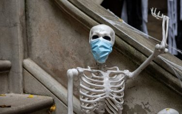 NEW YORK, NEW YORK - OCTOBER 27:  A skeleton wearing a protective mask is displayed at an Upper West Side home decorated for Halloween on October 27, 2020 in New York City. Many Halloween events have been canceled or adjusted with additional safety measures due to the ongoing coronavirus (COVID-19) pandemic.  (Photo by Alexi Rosenfeld/Getty Images)