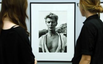 epa05096718 (FILE) A file photograph showing two visitors looking at the portrait of David Bowie from 1983 (Monte Carlo) taken by German-Australian photographer Helmut Newton, displayed at the Photography Museum - Helmut Newton Foundation in Berlin, Germany, 26 November 2014. According to reports quoting David Bowie's son and his official Facebook page, Bowie, 69, has died on 11 January 2016 after a battle with cancer. 'David Bowie died peacefully on 11 January 2016 surrounded by his family after a courageous 18 month battle with cancer. While many of you will share in this loss, we ask that you respect the family's privacy during their time of grief,' read a statement posted on the artist's official social media accounts.  EPA/STEPHANIE PILICK