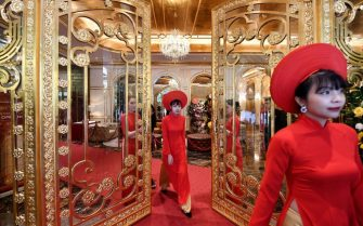 TOPSHOT - Staff wait to welcome guests in the lobby of the newly-inaugurated Dolce Hanoi Golden Lake hotel, the world's first gold-plated hotel, in Hanoi on July 2, 2020. (Photo by Manan VATSYAYANA / AFP) (Photo by MANAN VATSYAYANA/AFP via Getty Images)