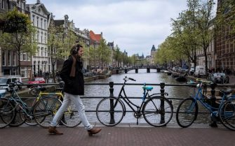 View of a canal in Amsterdam with a man walking on April 12, 2017. / AFP PHOTO / Aurore Belot        (Photo credit should read AURORE BELOT/AFP via Getty Images)