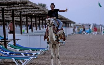 A young man rides a camel by the beach at the Egyptian Red Sea resort  of Sharm el-Sheikh on November 2, 2015.  A Russian passenger plane carrying 224 people and heading from Sharm el-Sheikh to the Russian city of Saint Petersburg crashed in Egypt's Sinai desert on October 31, killing everyone aboard.   AFP PHOTO / STR        (Photo credit should read STR/AFP via Getty Images)