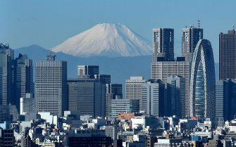 Japan's highest mountain, Mount Fuji (C) is seen behind the skyline of the Shinjuku area of Tokyo on December 6, 2014. Tokyo stocks closed at a seven-year high on December 5 -- extending their winning streak for a sixth straight day -- as a falling yen and oil prices continue to boost investor spirit.  AFP PHOTO / KAZUHIRO NOGI        (Photo credit should read KAZUHIRO NOGI/AFP via Getty Images)