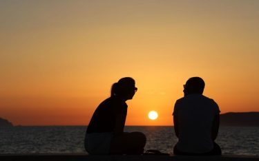 A couple watches the sunset over the Aegadian Islands in Trapani, Sicily, on August 16, 2017. (Photo by ludovic MARIN / AFP)        (Photo credit should read LUDOVIC MARIN/AFP via Getty Images)