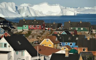 ILULISSAT, GREENLAND - JULY 30: Icebergs floating at the mouth of the Ilulissat Icefjord loom behind the town center on July 30, 2019 in Ilulissat, Greenland. As the Earth's climate warms summers have become longer in Ilulissat, allowing fishermen a wider period to fish from boats on open waters and extending the summer tourist season. Long term benefits are uncertain, however, as warming waters could have a negative impact on the local fish and whale population.  (Photo by Sean Gallup/Getty Images)
