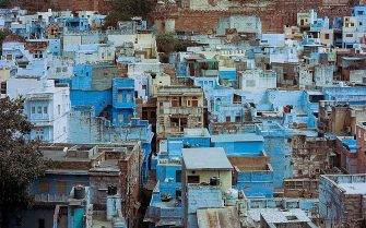 Houses are seen below the walls of Mehrangarh Fort in the old quarters of the Indian city of Jodhpur on March 17, 2016.  Rajasthan's 'Blue City' Jodhpur is famed for the blue-painted walls of the old city that sits in the shadow of the Mehrangarh Fort. Used to denote Brahmin, or upper-caste, households, discouraging looters if the city ever came under attack, many of Jodhpurs buildings retain the traditional blue paintwork that has come to signify the city.  / AFP / Rebecca CONWAY        (Photo credit should read REBECCA CONWAY/AFP via Getty Images)