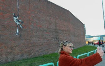 People take photographs of an artwork which has appeared on the wall of the former prison in Reading, Berkshire. Picture date: Monday March 1, 2121. PA Photo. Although its has not been officially claimed as the work of Banksy, the picture bares a resemblance to the artists other works. Photo credit should read: Steve Parsons/PA Wire (Photo by Steve Parsons/PA Images via Getty Images)