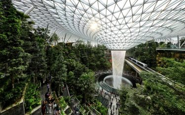 SINGAPORE - APRIL 11:  The skytrain rides past the Rain Vortex at the Jewel Changi Airport on April 11, 2019 in Singapore. Officially opening on April 17, Singapore's Changi Airport Jewel includes a 40-meter indoor waterfall contained under a steel-and-glass dome reportedly built for SGD 1.7 billion. (Photo by Suhaimi Abdullah/Getty Images)