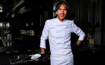 """Italian Michelin-starred chef Davide Oldani, wearing protective gloves, poses at his flagship restaurant """"D'O"""" in San Pietro all'Olmo, Cornaredo, west of Milan, on May 21, 2020, as the country eases its lockdown aimed at curbing the spread of the COVID-19 infection, caused by the novel coronavirus. - Renowned chef Davide Oldani considers himself rather privileged with his spacious starred restaurant, the D'O in Cornaredo, which room and tables are large enough to easily comply with the rules of distancing. Still closed, he has taken advantage of the quarantine period to carry out some work. (Photo by MIGUEL MEDINA / AFP)"""
