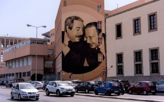 PALERMO, ITALY - AUGUST 8: A large mural, created by Rosk and Loste, two artists from Caltanissetta, which portrays judges Giovanni Falcone and Paolo Borsellino killed by the mafia and reproduces the famous shot of photographer Tony Gentile who sees the two talking to each other smiling on the facade of the Istituto Nautico Gioeni - Trabia in Palermo situation in the area of Cala on August 8, 2019 in Palermo, Italy. (Photo by Stefano Montesi - Corbis/Getty Images)