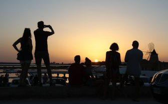People enjoy sunset in front of windmills and salternes on August 15, 2017 in Marsala, Sicily. (Photo by ludovic MARIN / AFP)        (Photo credit should read LUDOVIC MARIN/AFP via Getty Images)
