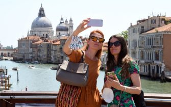 Tourists take selfie pictures on the Ponte dell'Accademia bridge over the grand canal in Venice on June 03, 2021. (Photo by ANDREA PATTARO / AFP) (Photo by ANDREA PATTARO/AFP via Getty Images)
