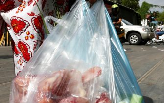 epa09409082 A woman carries plastic bags of meat and vegetable on a street in Phnom Penh, Cambodia, 11 August 2021. According to Cambodian Ministry of Environment spokesman Neth Pheaktra, people in Phnom Penh generated 2,700 to 3,000 tons of garbage every day, of which more than 20 percent is plastic waste as COVID-19 encouraged people to use more plastic as preventive materials and packaging for food.  EPA/MAK REMISSA