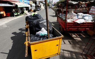 epa09409079 Workers travel with a garbage cart loaded plastic bags on a street in Phnom Penh, Cambodia, 11 August 2021. According to Cambodian Ministry of Environment spokesman Neth Pheaktra, people in Phnom Penh generated 2,700 to 3,000 tons of garbage every day, of which more than 20 percent is plastic waste as COVID-19 encouraged people to use more plastic as preventive materials and packaging for food.  EPA/MAK REMISSA