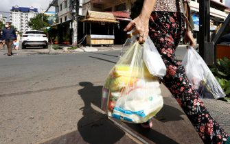 epa09409080 A woman carries plastic bags of meat and vegetable on a street in Phnom Penh, Cambodia, 11 August 2021. According to Cambodian Ministry of Environment spokesman Neth Pheaktra, people in Phnom Penh generated 2,700 to 3,000 tons of garbage every day, of which more than 20 percent is plastic waste as COVID-19 encouraged people to use more plastic as preventive materials and packaging for food.  EPA/MAK REMISSA
