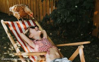 The Comedy Pet Photography Awards 2021 Catherine Falls County Antrim United Kingdom Title: Sunbathers Description: Barbara-Ann wants to sunbathe too. Animal: Chicken Location of shot: Ireland