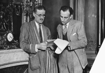 Author James Joyce looks at a set of papers with another man.