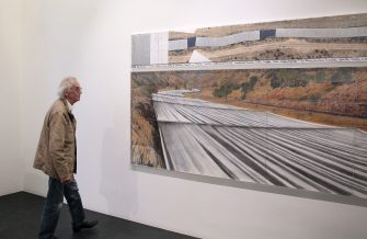 """Bulgarian-born artist Christo poses on November 26, 2010 next to one of his works as part of his exhibition """"Project for the Arkansas River, State of Colorado"""" that will be on show until January 23, 2010 at the Guy Pieters Gallery in Paris.         AFP PHOTO/JACQUES DEMARTHON (Photo by JACQUES DEMARTHON / AFP)        (Photo credit should read JACQUES DEMARTHON/AFP via Getty Images)"""