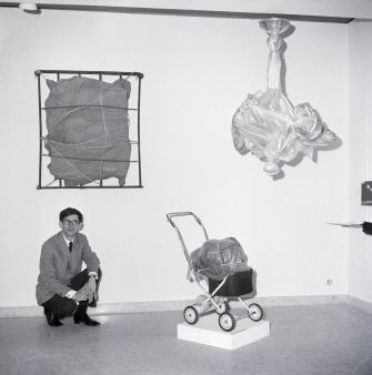 """(Original Caption) 11/29/1963-Rome, Italy- The art of wrapping, called """"Empaquetage"""" by artist Christo, features all shapes and sizes creatively covered...""""The purpose of which is to reveal the loving form of mystery,"""" he says. The 28-year-old, Bulgarian-born artist creates with such wrappings as cellophane, canvas or blankets and ties the objects with any string available at the time. Here, Christo is seen surrounded by his """"Objects D'Art"""" which he displayed at the La Salita Gallery in Rome, Italy."""
