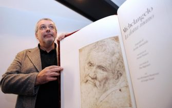 """FMR (Franco Maria Ricci)'s scientific director Flaminio Gualdoni (L) presents on October 9, 2008 in Paris, a Michelangelo monography to be sold for 100.000 euros. FMR publishing house printed only 99 copies of its """"most beautiful book of the world"""", created by thirteen craftmanshops with a marble cover, 83 original photographs by Aurelio Amendola and a text calligraphed on parchment. AFP PHOTO BORIS HORVAT (Photo credit should read BORIS HORVAT/AFP via Getty Images)"""