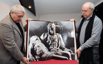 """FMR (Franco Maria Ricci)'s scientific director Flaminio Gualdoni (L) and general director Antonio Pistilli present on October 9, 2008 in Paris """"La Pieta"""" included in a Michelangelo monography to be sold for 100.000 euros. FMR publishing house printed only 99 copies of its """"most beautiful book of the world"""", created by thirteen craftmanshops with a marble cover, 83 original photographs by Aurelio Amendola and a text calligraphed on parchment. AFP PHOTO BORIS HORVAT (Photo credit should read BORIS HORVAT/AFP via Getty Images)"""