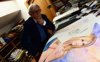 TO GO WITH AFP STORY BY PHILIP SIUBERSKI - Italian artist Milo Manara poses at his working table with drawings of French icon Brigitte Bardot, on May 13, 2016 in his house near Verona.   / AFP / GIUSEPPE CACACE        (Photo credit should read GIUSEPPE CACACE/AFP via Getty Images)