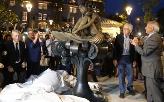 Onlookers including French actress Brigitte Bardot's fourth and current husband Bernard d'Ormale (2R) gather beside a statue of Bardot during its inauguration in Saint-Tropez on September 28, 2017. The statue is based on an illustration - watercolour by Milo Manara.  / AFP PHOTO / VALERY HACHE / RESTRICTED TO EDITORIAL USE - MANDATORY MENTION OF THE ARTIST UPON PUBLICATION - TO ILLUSTRATE THE EVENT AS SPECIFIED IN THE CAPTION        (Photo credit should read VALERY HACHE/AFP via Getty Images)