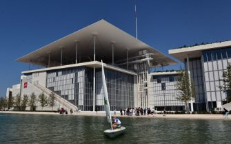 "A man sails in front of the newly built Athens national Opera (L) and library buildings at the Stavros Niarchos Cultural Center in an Athens suburb on June 24, 2016.  A leading Greek foundation on Friday unveiled a sprawling new park, opera and national library in southern Athens designed to ""give hope"" to a country brought low by a six-year economic crisis. The 1,400-seat opera, library and adjoining park designed by famed Italian architect Renzo Piano cost nearly 600 million euros ($680 million) and took eight years to design and build. The new Stavros Niarchos Cultural Center, expected to fully open in mid-2017, occupies 20 hectares (50 acres) overall near the coast of Faliro in southern Athens. / AFP / LOUISA GOULIAMAKI        (Photo credit should read LOUISA GOULIAMAKI/AFP via Getty Images)"
