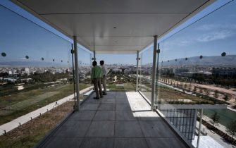 "People enjoy the view from a viewing point atop the newly built Athens national Opera at the Stavros Niarchos Cultural Center in an Athens suburb on June 24, 2016.  A leading Greek foundation on Friday unveiled a sprawling new park, opera and national library in southern Athens designed to ""give hope"" to a country brought low by a six-year economic crisis. The 1,400-seat opera, library and adjoining park designed by famed Italian architect Renzo Piano cost nearly 600 million euros ($680 million) and took eight years to design and build. The new Stavros Niarchos Cultural Center, expected to fully open in mid-2017, occupies 20 hectares (50 acres) overall near the coast of Faliro in southern Athens. / AFP / LOUISA GOULIAMAKI        (Photo credit should read LOUISA GOULIAMAKI/AFP via Getty Images)"
