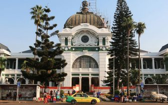 People stand outside the Maputo railway station, one of the many buildings left from the Portuguese colonial era in Maputo, on the eve of the 40th anniversary of Mozambique's independence from Portugal on June 24, 2015. Upon gaining its independence, Mozambique directly entered a 16-year-long destructive civil war which didnt allow the young Mozambican state to maintain its infrastructure. Mozambique and Angola this year mark four decades of independence from Portugal, with robust economic growth rates buoyed by abundant natural resources giving the southern African nations reason to celebrate. AFP PHOTO / ADRIEN BARBIER        (Photo credit should read ADRIEN BARBIER/AFP via Getty Images)