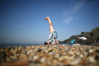 SHEERNESS, ENGLAND - SEPTEMBER 05:  A woman practices yoga on the beach on September 5, 2013 in Sheerness, England. Southern England is enjoying a couple of days of late summer sunshine with temperatures today expected to peak at 30C, before predicted rain and cooler temperatures are pushed in tonight.  (Photo by Peter Macdiarmid/Getty Images)