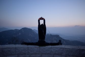 In a photo taken early on January 11, 2015 a hiker stretches at a viewpoint overlooking the Seoul city skyline and Bukhan mountains. Early morning hikers and photographers are a familiar sight across the city's many viewpoints. AFP PHOTO / Ed Jones        (Photo credit should read ED JONES/AFP via Getty Images)