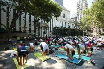 NEW YORK - JUNE 30:  People participate in a free outdoor yoga class in Bryant Park on June 30, 2009 in New York City.  After weeks of unseasonably wet weather, New York and New England have been experiencing dry and warm days which have brought about a flurry of activity in area parks and recreation areas.  (Photo by Spencer Platt/Getty Images)