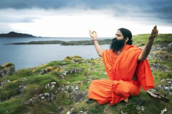Indian yoga guru Baba Swami Ramdev practices yoga on the island of Little Cumbrae off the west coast of Scotland, on September 27, 2009. According to some British newspapers, Sam and Sunita Podda, an Indian couple who own the island, plan to welcome pilgrims to yoga retreats on the island within the next 18 months. AFP PHOTO/Andy Buchanan (Photo credit should read Andy Buchanan/AFP via Getty Images)
