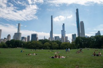 NEW YORK, NEW YORK - AUGUST 23: People gather in Sheep Meadow, Central Park with Steinway Tower and Billionaire's Row in the background as the city continues Phase 4 of re-opening following restrictions imposed to slow the spread of coronavirus on August 23, 2020 in New York City. Steinway tower, located at 111 West 57th Street is the world's skinniest skyscraper when looking at it's height-to-width ratio. The building stands at 1,428 feet tall. (Photo by Alexi Rosenfeld/Getty Images)