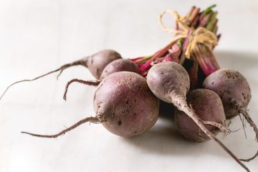 Bundle of young organic garden beetroot over white marble background. . (Photo by: Natasha Breen/REDA&CO/Universal Images Group via Getty Images)