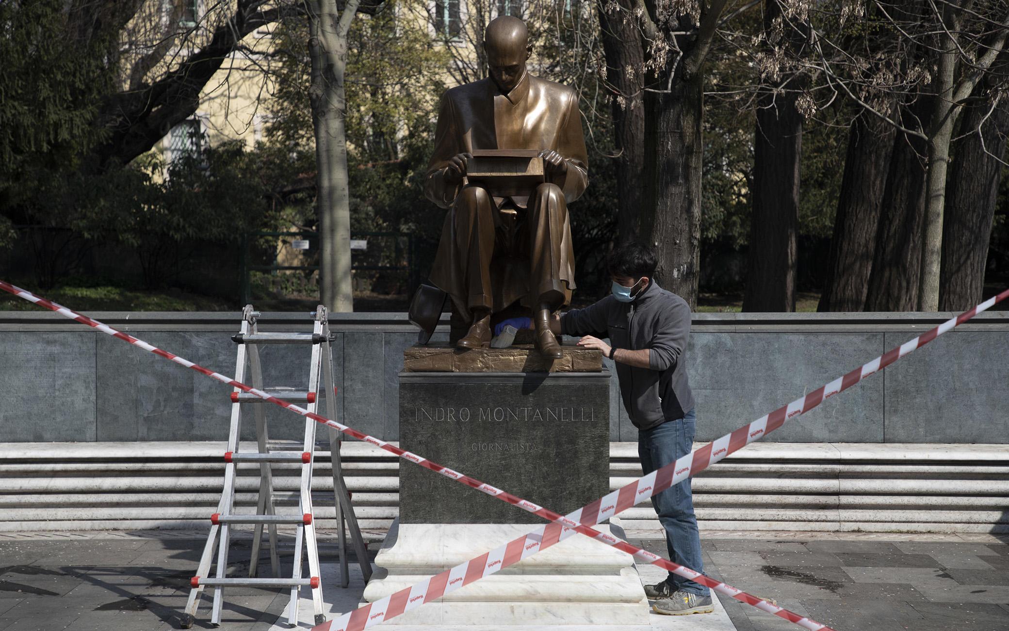 Dopo che ieri la statua di Indro Montanelli situata nei giardini di Porta Venezia è stata nuovamente imbrattata, i restauratori puliscono i graffiti fatti con la vernice, Milano, 12 marzo 2021. ANSA/ MARCO OTTICO