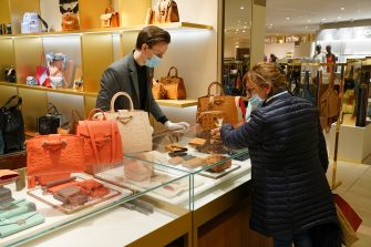 BERLIN, GERMANY - MAY 05: A woman wearing a surgical mask who said she did not mind being photographed shops at a counter of luxury handbags at the KaDeWe department store on the first day KaDeWe fully reopened during the novel coronavirus crisis on May 05, 2020 in Berlin, Germany. Germany is carefully lifting lockdown measures nationwide in an attempt to raise economic activity.  (Photo by Sean Gallup/Getty Images)