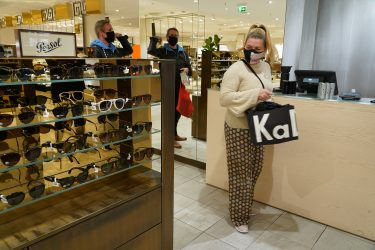 BERLIN, GERMANY - MAY 05: A woman wearing a protective face mask who said she did not mind being photographed waits to pay in a section selling sunglasses at the KaDeWe department store on the first day KaDeWe fully reopened during the novel coronavirus crisis on May 05, 2020 in Berlin, Germany. Germany is carefully lifting lockdown measures nationwide in an attempt to raise economic activity.  (Photo by Sean Gallup/Getty Images)