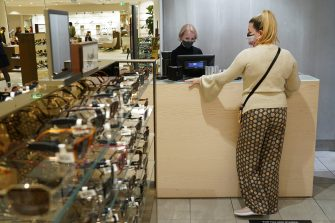 BERLIN, GERMANY - MAY 05: A woman wearing a protective face mask who said she did not mind being photographed pays for a puchase in a section selling sunglasses at the KaDeWe department store on the first day KaDeWe fully reopened during the novel coronavirus crisis on May 05, 2020 in Berlin, Germany. Germany is carefully lifting lockdown measures nationwide in an attempt to raise economic activity.  (Photo by Sean Gallup/Getty Images)