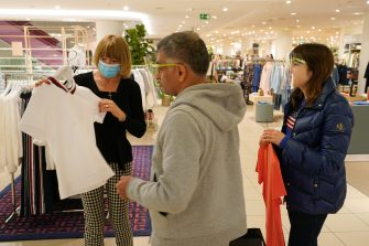 BERLIN, GERMANY - MAY 05: A sales assistant wearing a surgical mask assists customers wearing visors who said they did not mind being photographed at the KaDeWe department store on the first day KaDeWe fully reopened during the novel coronavirus crisis on May 05, 2020 in Berlin, Germany. Germany is carefully lifting lockdown measures nationwide in an attempt to raise economic activity.  (Photo by Sean Gallup/Getty Images)
