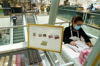 BERLIN, GERMANY - MAY 05: A sales assistant wearing a surgical mask sells macaroons at the KaDeWe department store on the first day KaDeWe fully reopened during the novel coronavirus crisis on May 05, 2020 in Berlin, Germany. Germany is carefully lifting lockdown measures nationwide in an attempt to raise economic activity.  (Photo by Sean Gallup/Getty Images)