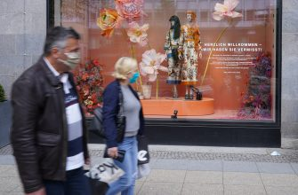 BERLIN, GERMANY - MAY 05: People wearing protective face masks walk past the KaDeWe department store on the first day KaDeWe fully reopened during the novel coronavirus crisis on May 05, 2020 in Berlin, Germany. Germany is carefully lifting lockdown measures nationwide in an attempt to raise economic activity.  (Photo by Sean Gallup/Getty Images)