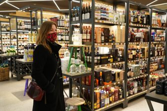 BERLIN, GERMANY - MAY 05: A woman wearing a protective face mask who said she did not mind being photographed shops in the liquor section at the KaDeWe department store on the first day KaDeWe fully reopened during the novel coronavirus crisis on May 05, 2020 in Berlin, Germany. Germany is carefully lifting lockdown measures nationwide in an attempt to raise economic activity.  (Photo by Sean Gallup/Getty Images)