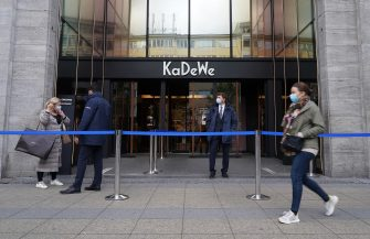BERLIN, GERMANY - MAY 05: A young woman wearing a protective face mask walks past the KaDeWe department store on the first day KaDeWe fully reopened during the novel coronavirus crisis on May 05, 2020 in Berlin, Germany. Germany is carefully lifting lockdown measures nationwide in an attempt to raise economic activity.  (Photo by Sean Gallup/Getty Images)