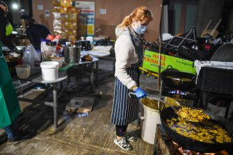 LONDON, ENGLAND - MAY 05: A volunteer wearing a mask is seen cooking at a kitchen in an underground carpark run by the Hare Krishna on May 5, 2020 in London, England. The Hare Krishna are preparing and distributing meals to vulnerable people and communities across London in light of the Coronavirus pandemic. The country continues quarantine measures intended to curb the spread of Covid-19, but the infection rate is falling, and government officials are discussing the terms under which it would ease the lockdown. (Photo by Peter Summers/Getty Images)