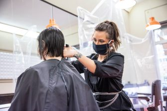 BERLIN, GERMANY - MAY 04: A hairdresser cuts customer hair at a hair salon that opened today for the first time since March during the novel coronavirus (Covid-19) crisis on May 4, 2020 in Berlin, Germany. Barber shops and hair salons are reopening this week nationwide as authorities carefully lift lockdown measures that had been imposed to stem the spread of the virus. (Photo by Maja Hitij/Getty Images)