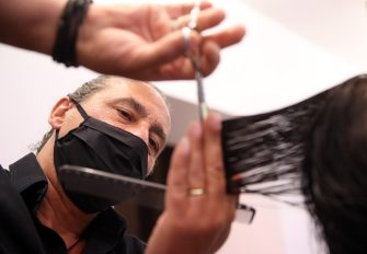 LEONBERG, GERMANY - MAY 04: Hairdresser Janni Ossas works with a client at his Kertu Hair Professionals hair salon that opened today for the first time since March during the novel coronavirus crisis on May 4, 2020 in Leonberg, Germany. Barber shops and hair salons are reopening this week nationwide as authorities carefully lift lockdown measures that had been imposed to stem the spread of the virus. (Photo by Alex Grimm/Getty Images)